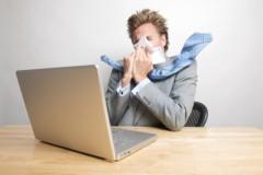 Mann am Laptop niest