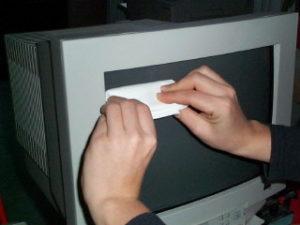Hände mit Desinfektionstuch säubern Monitor